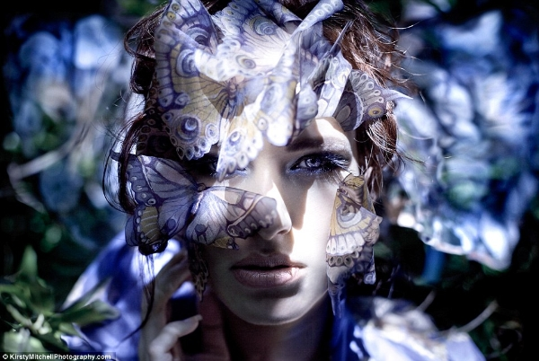 Một bức ảnh chụp cận cảnh người mẫu dưới ánh sáng mặt trời, nhìn mọi thứ qua tấm màn che kết từ những con bướm giấy.