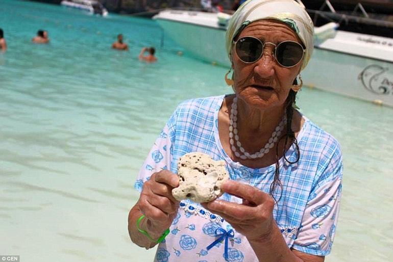 Bà Lena  đang cầm một mảnh san hô, phía sau là nước biển trong xanh như pha trên một bãi biển nhiệt đới.